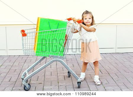 Happy Little Girl Child And Trolley Cart With Colorful Shopping Bags Walking In City