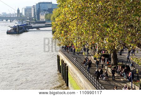 Pedestrians on the North Bank of the River Thames, London