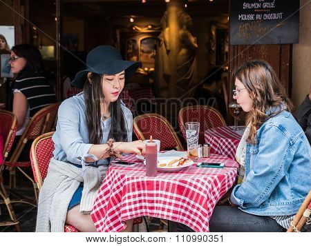 Young Women Friends Have Afternoon Snack At Montmartre Cafe, Paris