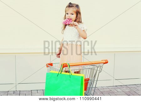 Happy Little Girl Child With Sweet Caramel Lollipop And Colorful Shopping Bags In Trolley Cart