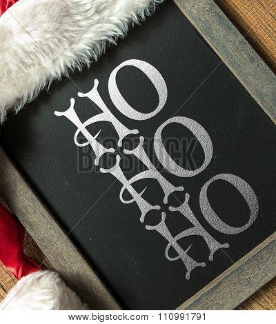 HO HO HO written on blackboard with santa hat