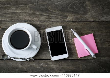 Phone With Cup Of Coffee On Old Wooden Desk.