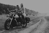 Постер, плакат: photo biker couple on a motorcycle in the field