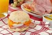 stock photo of orange-juice  - An english muffin with ham egg and cheese - JPG