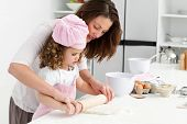 image of mother child  - Mother and daughter using a rolling pin together in the kitchen - JPG