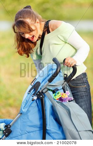 Laughing young mother looking in stroller while walking in park