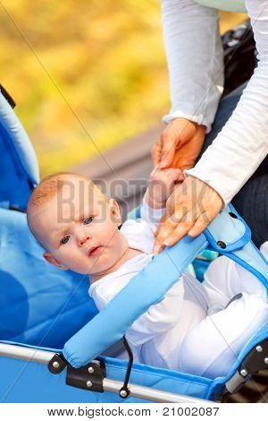 Surprised baby girl sitting in stroller in park and holding mother's hand