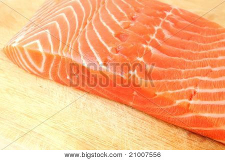 fresh raw salmon fish piece over wooden board isolated on white background