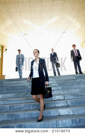 Portrait of confident business leader walking down stairs with several employees behind