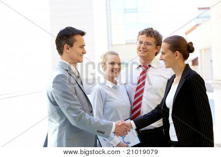 Retrato de duas handshaking de parceiros de negócios depois de fazer acordo com dois funcionários perto por