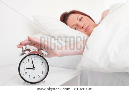 Attractive red-haired female waking up thanks to an alarm clock in the bedroom