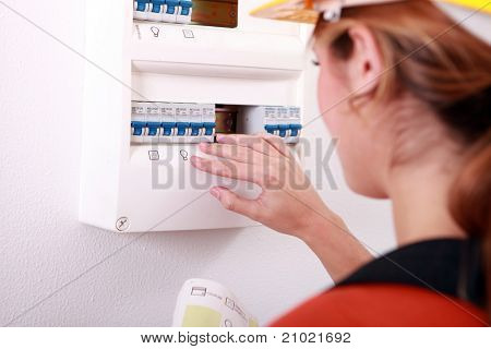 Woman checking electric meter