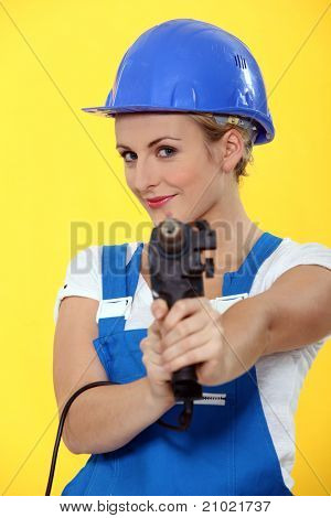 Pretty young woman using drill like a gun