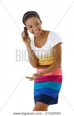 Laughing pretty girl standing in striped dress in studio on mobile phone call.?