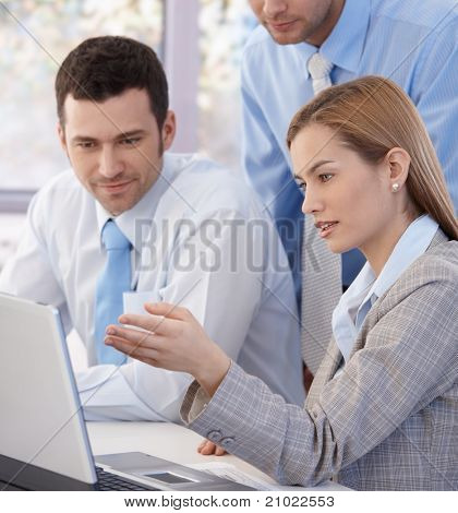 Closeup photo of young colleagues working together in bright office, looking at screen.?