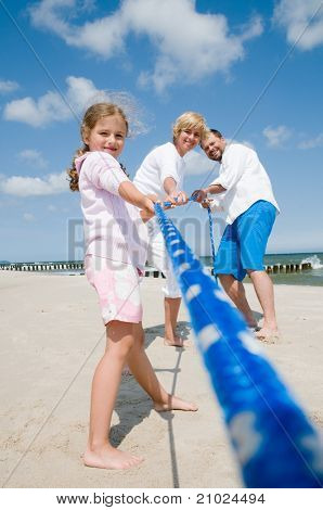 Tug of war - family playing on the beach