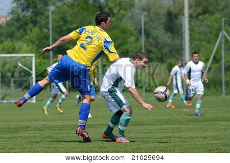 KAPOSVAR, HUNGARY - JUNE 11: Erik Judak (in yellow) in action at the Hungarian National Championship under 13 game between Kaposvari Rakoczi FC and Bajai LSE on June 11, 2011 in Kaposvar, Hungary.