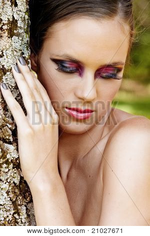 beautiful woman with dramatic eye makeup and long eyelashes wearing grey manicure standing by the tree looking down.