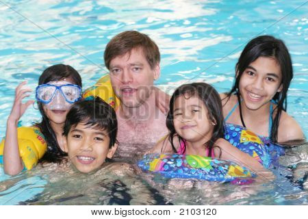 Family Enjoying Swimming In The Pool