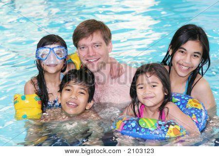 Family Enjoying Swimming In The Pool