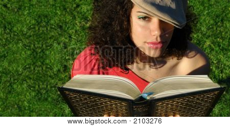 Young Woman Reading A Book In The Evening