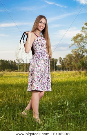Stylish woman in dress with bag outdoor. Summer shopping time