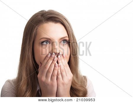 Portrait of a surprised young woman with hands over her mouth laughing against white background