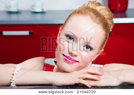 Closeup portrait of girl in interior of red modern kitchen