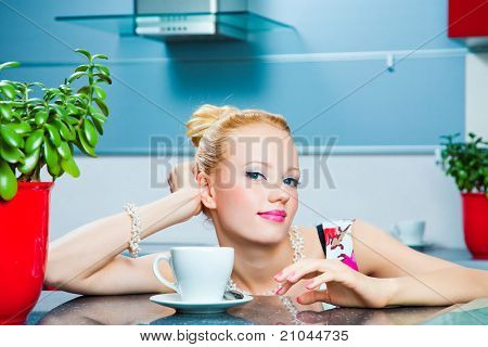 romantic girl with cup of coffee in interior of kitchen
