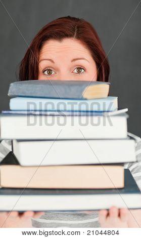 junge Frau Hidding hinter einen Stapel von Büchern