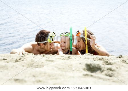 Portrait of cheerful couple and their son in diving equipment lying on sandy shore