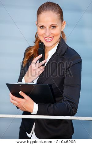 Leaning on railing at office building smiling modern business woman holding mobile and clipboard