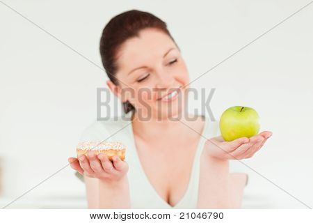 Pretty Woman Posing While Holding A Donut And A Green Apple