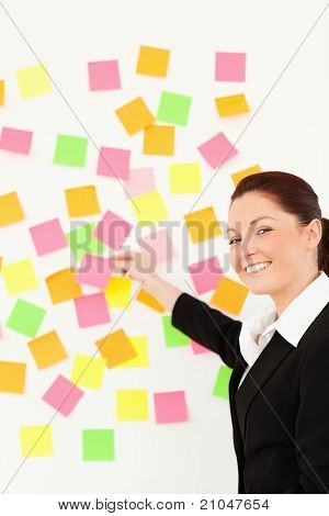 Smiling Woman Putting Repositionable Notes On A White Wall