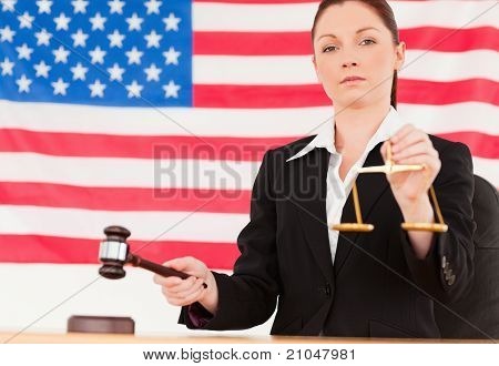 Close Up Of A Cute Judge Knocking A Gavel And Holding Scales Of Justice