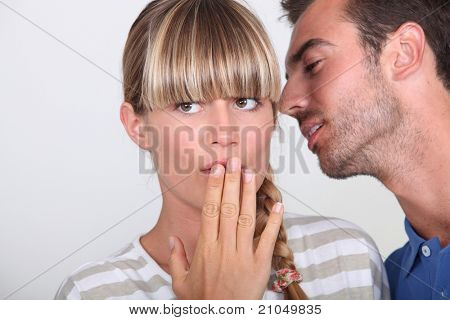 Man telling a secret to a woman
