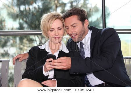 Close business colleagues looking at phone