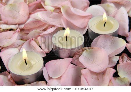 Drei brennenden Kerzen umgeben von Rosenblüten