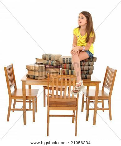 Child Sitting On Table Of Books