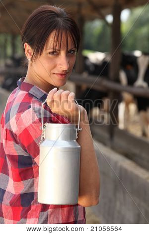 Farm worker holding milk container