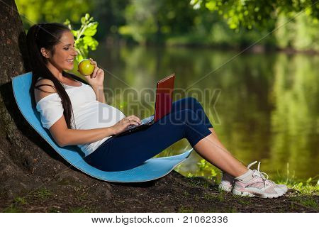 Young Pregnant  Woman With Laptop And An Apple Sits In The Park.