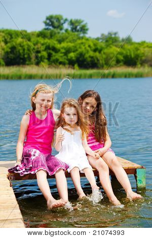 Kids sitting on the river bridge in a sunny day