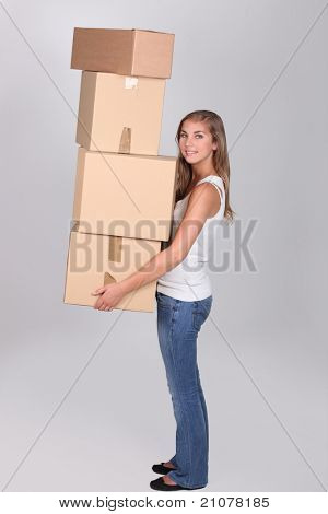 Young woman carrying four large packing boxes