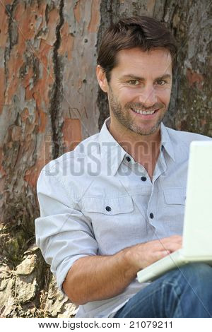 Man on laptop under tree