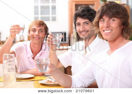 Three young men eating a meal together and drinking water