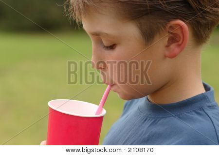 Child Drinking Through A Straw