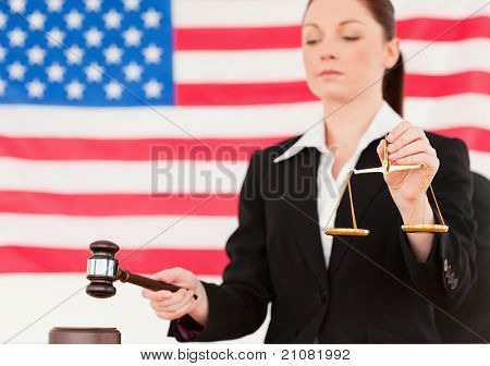 Close up of a young judge knocking a gavel and holding scales of justice with an American flag in the background