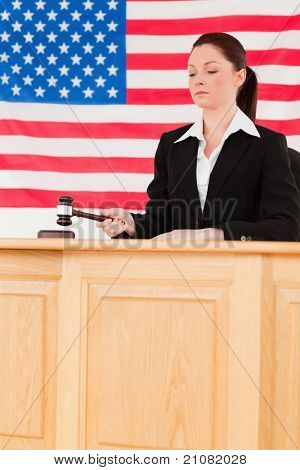 Focused judge knocking a gavel with an American flag in the background