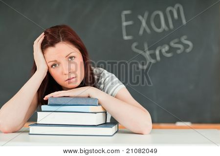 Young student stressed by her examinations in a classroom