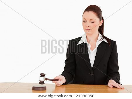 Young judge knocking a gavel against a white background